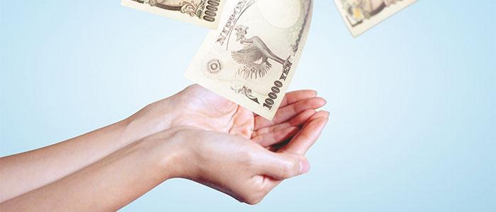 舞うお金を手に入れる女性の手